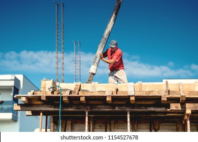 Industrial worker laying concrete with automatic tube pump. Workman on site with mortar and construction activities
