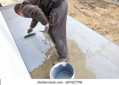 Industrial Worker On Construction Site Laying Sealant For Waterproofing  Cement. Worker Apply Liquid Foil To