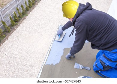 Industrial worker on construction site laying sealant for waterproofing cement. Worker apply liquid foil to the terrace. Workers applying a memory shape polymer waterproofing.