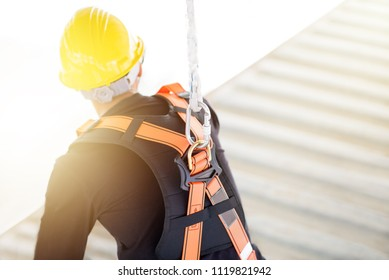 Industrial Worker with safety protective equipment loop hanging on the back sitting above the container, safety concept