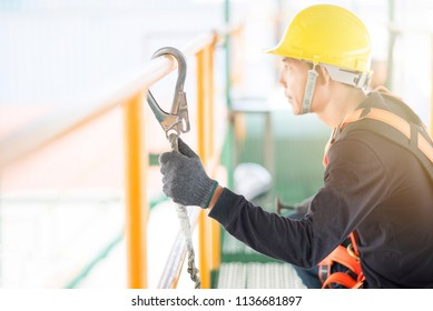 Industrial Worker with safety protective equipment loop hanging on the bar besides