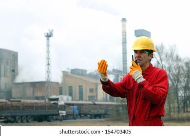 Industrial worker. Sugar Refinery Plant. Portrait of a worker using walkie-talkie in sugar refinery.