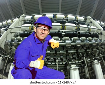 Industrial worker in textile mill squatting and showing thumbs up