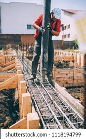 industrial worker using concrete pump for pouring concrete into foundation
