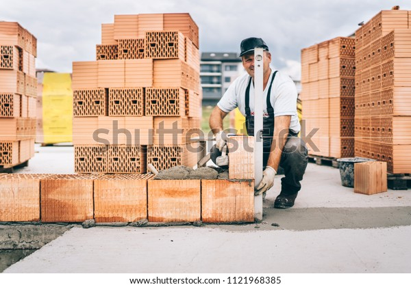 Industrial worker using trowel and hammer for building exterior walls with bricks and mortar