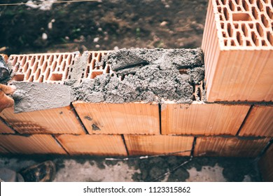 Industrial worker using trowel and tools for building exterior walls with bricks, mortar and concrete