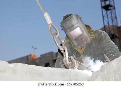 Industrial worker Welder welding metal rebar in reinforced concrete panels during hoisting construction works