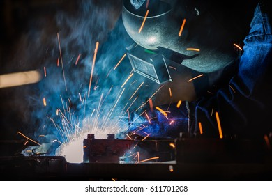 Industrial worker is welding assembly automotive part in factory
