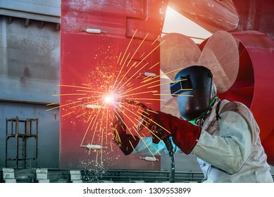Industrial Worker welding at the factory ship repair with protective equipment mask, PPE marks welder at floating dry dock in shipyard on rudder, propeller and shaft background.
