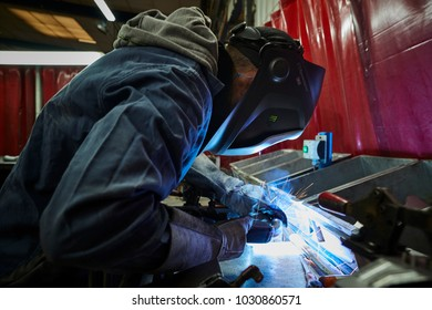 Industrial worker welding metal at the factory, wearing protective mask