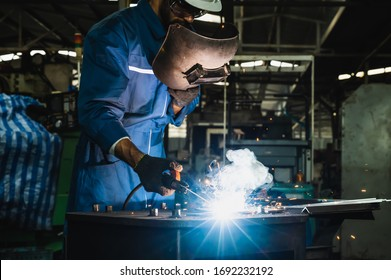 Industrial worker welding metal with many sharp sparks
