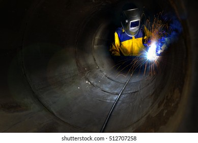 Industrial worker welding metal and many sharp sparks inside piping construction with confined space .