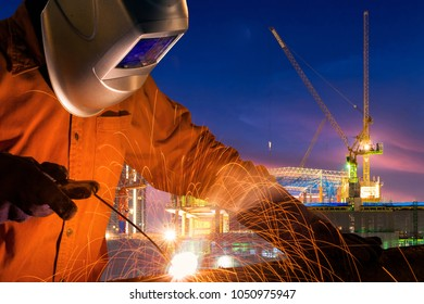 Industrial worker welding steel structure for infrastructure building project with construction site background.
