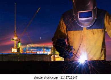 Industrial worker welding steel structure for infrastructure building project with construction site in background.