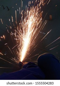 Industrial worker without safety gloves are using grinding tools on the metal floor to be smoothed so that sparks arise