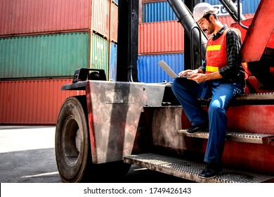 Industrial worker working at cargo freight logistic warehouse for import export, foreman use computer for online internet communication , Import and export business.