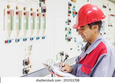 Industrial worker writes on a paper conditions from a control panel.Shallow doff