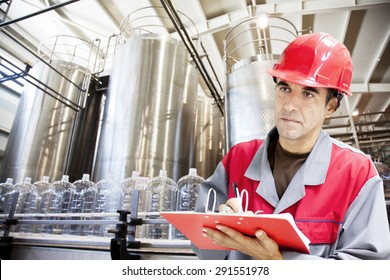 Industrial worker writes on a paper conditions in a filling line production of drinking water.Shallow doff