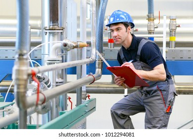 industrial workers inspect the technology of a plant for function - assembler in working clothes