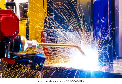 industrial yellow robot welder close - up conduct welding of metal parts, metal droplets are beautifully sprinkled in all directions