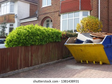 Industrial yellow rubbish skip on driveway. Selective focus on full metal bin with space to add text on surrounding background of green bush, wooden fence, houses. Renovate, moving, clearance concept.