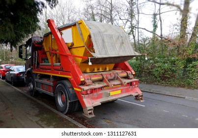 Industrial yellow rubbish skip with sheet cover top, loaded securely on back of truck. Space to add own text on road surface & green bush fence in background. House clearance, removal business concept