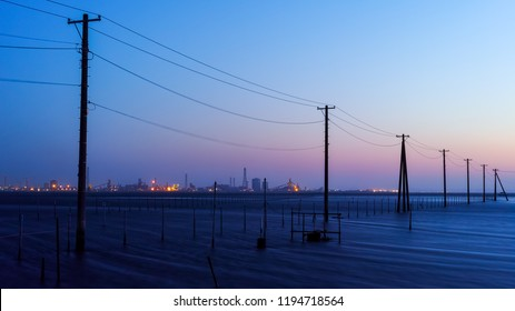 Industrial zone which is visible in the distance and the sea and the telephone poles