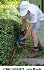 An industrious man prunes a hedge with electric pruning shears leaving a long trail of leaf clippings behind him on a sunny summer day