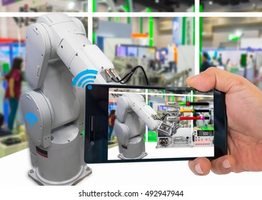 Industry 4.0 and Augmented reality for industry concept. Hand holding smart phone with A/R system control and diagnosis application on automate robot arm in smart manufacturing background.