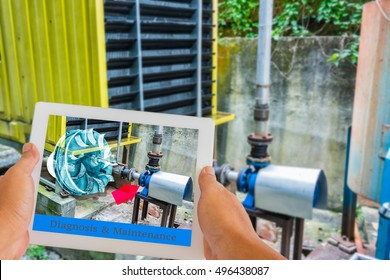 Industry 4.0 and Augmented reality for industry concept. Hand holding tablet with A/R maintenance application to identify machine part repair with refrigeration container in factory background.