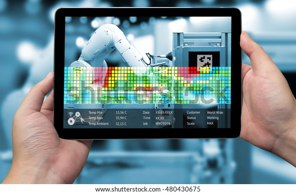 Industry 4.0 concept .Man hand holding tablet and Blue tone of Augmented reality screen with automate wireless Robot arm for measurement temperature software in smart factory blur background