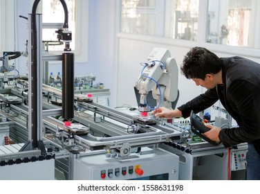 industry 4.0 concept: Man (engineer) is holding product and teaching robotic arm the points with control panel (teach pendant) on smart factory production line background. Selective Focus.