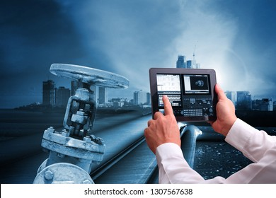 Industry 4.0 concept , Man hand holding tablet or cell phone  Augmented reality screen software and blue tone of automate wireless  pipelines
