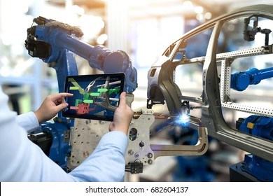 Industry 4.0 concept . Man hand holding tablet with performance check screen software and automate wireless Robot arm in automobile smart factory background.