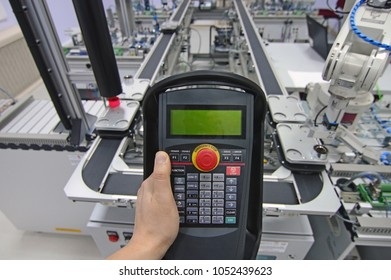 Industry 4.0 concept. Man is holding tablet to control smart factory manufacturing line which is equipped with sensors and robotic arm. industrial automation line.