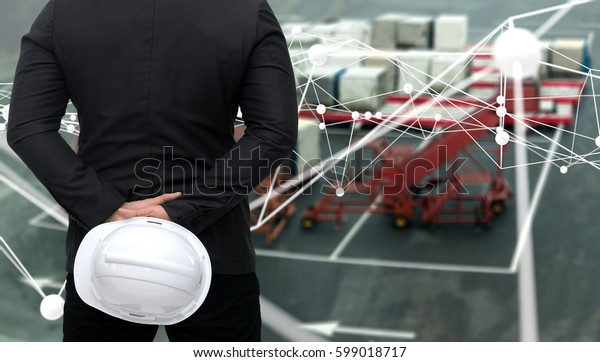 Industry 4.0 internet of things and smart airplane logistic concept. Business man suit stand back and holding white engineer hat with blur parcel boxes at airport background. Atom connect graphic.
