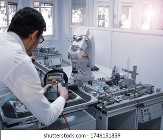industry 4.0: Man is holding teach pendant to control a robot arm which is integrated on smart factory production line. automation line which is equipped with sensors and robot arm. Selective Focus.