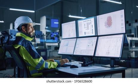 Industria 4.0 Fábrica moderna: Línea de producción del taller de controles de operador de instalaciones, utiliza equipos con pantallas que muestran interfaz de usuario compleja de procesos de funcionamiento de máquinas, controladores, programas de máquinas