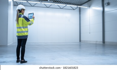 Industry 4.0 Modern Factory: Female Engineer is Stanging in Empty Warehouse and Using Digital Tablet Computer with Augmented Reality Software for Mapping Manufacturing Plant Room, Factory Layout.