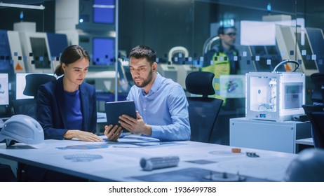 Industry 4.0 Modern Factory Meeting Room: Chief Engineer Holds Digital Tablet Computer, Shows it to Female Specialist, They Have Discussion. Design Electronic Machinery With Futuristic Design
