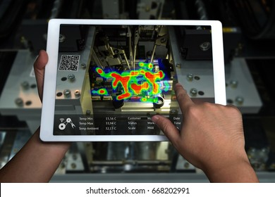 Industry 4.0 , qr code technology concept .Man hand holding tablet with augmented reality screen software to measure heat indicator , automate wireless integrated circuit machine in smart factory.
