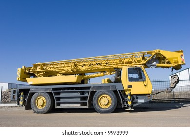 Industry background. Mobile crane truck and blue sky, ready for your text