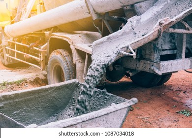 Industry concept. Concrete mixing truck service pouring cement in site building construction on daytime. Cement was poured into a wheelchair or cement trolley to make the floor.
