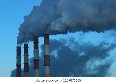 Industry, industry and ecology - gray-blue smoke from the red-white pipes of the plant (chemical plant power plant), thermal power plant against the blue clear sky