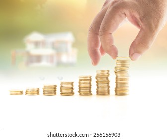 Industry Insurance concept: Human hand adding a golden coin in stacks of golden coins over blurred house on sunset background.