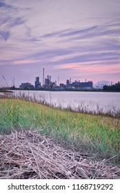 An industry location near the river Scheldt. The sun is setting but there's always activity in the industry.