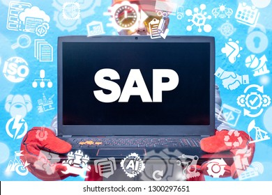 Industry man holding laptop with SAP abbreviation on a screen. SAP - software automation process erp industry technology.