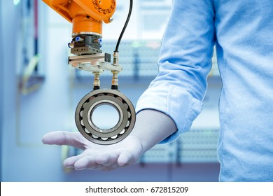 Industry robotic picked a spherical roller bearings on the right hand of engineers in blue tones color background, industry 4.0. concept