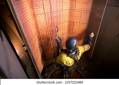 Industry Rope access NDT inspector wearing full body safety harness hardhat hanging in full arrest position commencing maintenance services inspection, written report at construction mine site Perth