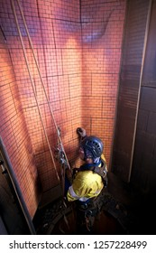 Industry rope access NDT inspector wearing full body safety harness hardhat hanging in full arrest position commencing wall thickness measurement inspection services, construction mine site Perth